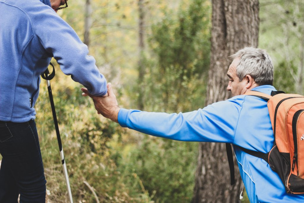 Violence Prevention Avalon East, NL: An older Caucasian male in a blue sweater and orange backpack takes the hand of another older Caucasian male wearing jeans and a blue jacket, holding a walking stick in the woods.