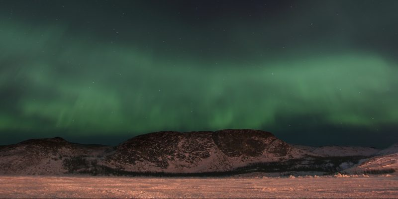 Violence Prevention Avalon East, NL:Taken by Jennie Williams of Nain, Labrador. Fading high to low, dark starry sky to green northern lights, with mountains and snow in the forefront.